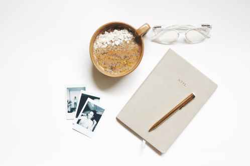 brown ceramic cup beside notebook and pen