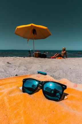 black framed blue sunglasses on orange textile