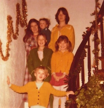 Five siblings standing on a staircase in pajamas, with christmas decorations all around.