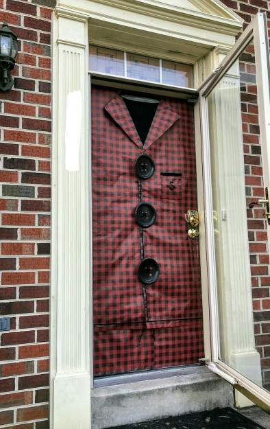 Front door decoated with black and red plaid wrapping paper in the style of flannel pajamas, with black paper plate buttons.