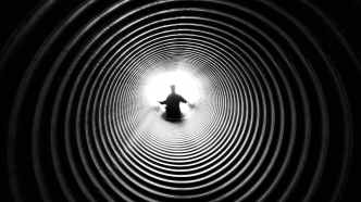 grayscale photography of person at the end of tunnel
