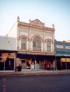 """Picture of an old building on a downtown main street. The building says """"Smith-Welch Memorial Library"""" on the front."""